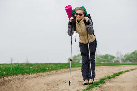 woman with trekking pole in hand , walking with backpack outdoors, Nordic walking Stock Photo