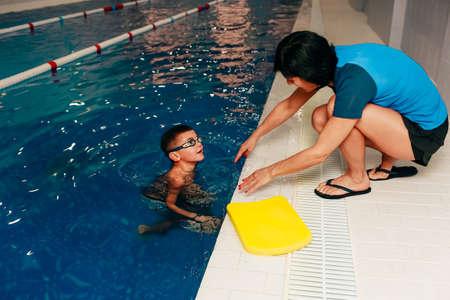 Zwemcoach voor kinderen traint de jongen. leren zwemmen bij het zwembad Stockfoto