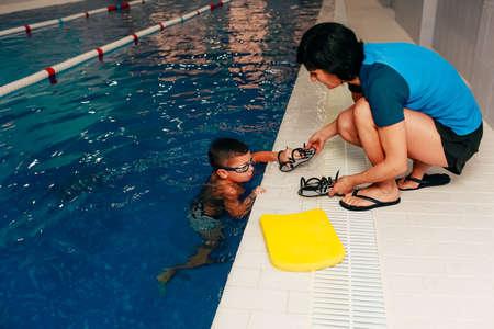 Het zwemmen van kinderen leidt de jongen op. leren zwemmen in het zwembad