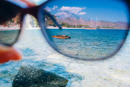 hand holding polarization sunglasses against blue sky and sea, summer vacation journey and concept, looking through glasses Stock Photo