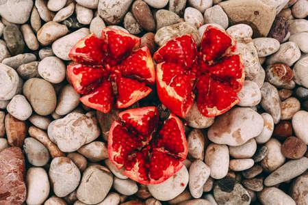 pomegranate on stony background, fruit on the beach close-up Stock Photo