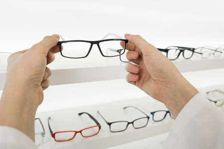 doctors hands holding glasses at optical store, out of focus showcase with many glasses. Zdjęcie Seryjne
