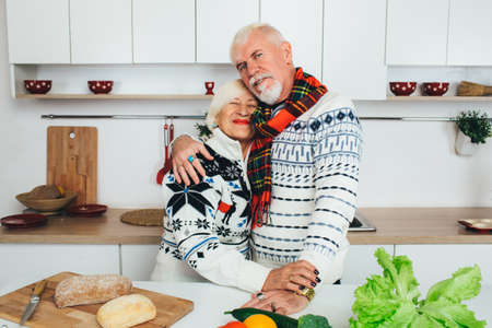 elderly couple embracing in the kitchen, seniors people spending time together at home. Zdjęcie Seryjne