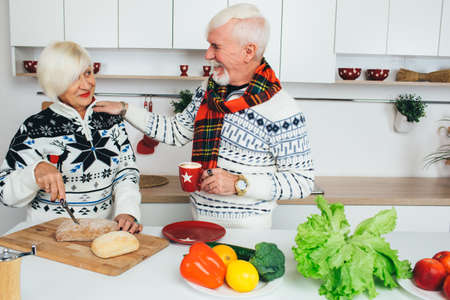 Elderly happy couple drinking tea and prepare healthy food standing at home in the kitchen, seniors people spending time together at home.
