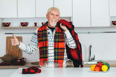 elderly man standing in outerwear, checkered scarf at home in the kitchen, looking at camera smiling and showing thumbs up