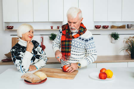 happy couple, elderly people preparing healthy food at the kitchen