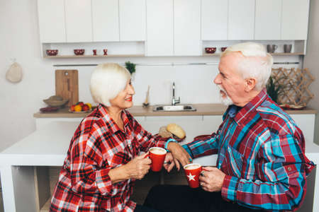 breakfast old people, elderly men and women drink together latte, being at home in the kitchen