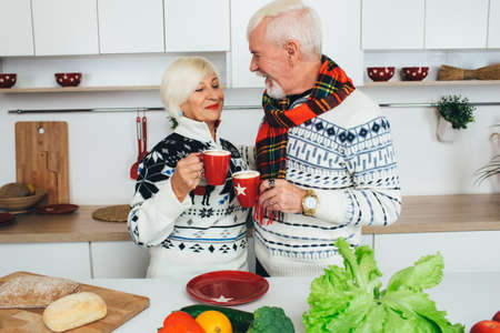 Elderly happy couple drinking latte standing at home in the kitchen, seniors people spending time together at home. Zdjęcie Seryjne