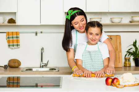 daughter helps her mother make a floury product , standing at white kitchen at home and laughing . Cooking together with kid Zdjęcie Seryjne