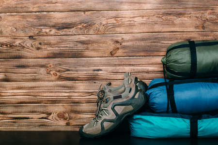 tourist lifestyle with trekking shoes, sleeping bags, tent on wooden background with copy space for text