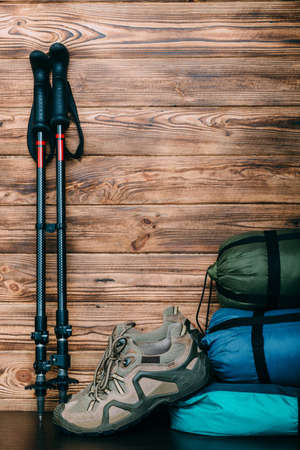 tourist lifestyle with trekking shoes, sleeping bags, tent and trekking poles on wooden background with copy space for text Zdjęcie Seryjne