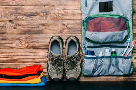 set of things for hiking and travel on wooden background. Items include trekking shoes, clothes and a set for hygiene