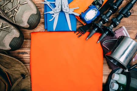 Top view of equipment for hiking and travel on wooden table with empty space in the middle. Items include trekking pole, shoes, multi tool, hat, towel, flashlight, hygiene products, cup