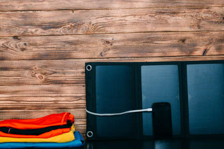 Portable Solar Battery,phone, and clothes - preparing for a hike on wooden background Zdjęcie Seryjne