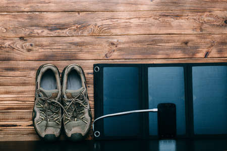 Portable Solar Battery,phone, and trekking shoes - preparing for a hike on wooden background