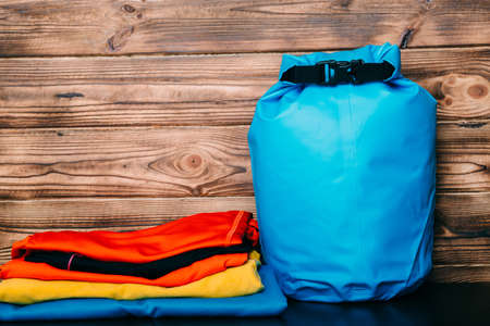 Swimming waterproof bag and clothes on wooden background Zdjęcie Seryjne