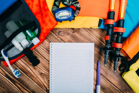 Top view of hiking accessories, journey concept background, Blank notebook and equipment for hiking on wooden table.