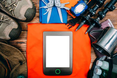 hiking accessories, trip concept background, male hand touches the tablet, top view