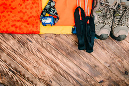 trip schedule with trekking shoes, clothes and accessories on an brown wooden table. Top view with empty space