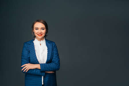 Portrait confident business woman . Confident young stylish woman in business clothes looking at camera with smile while standing against gray background Zdjęcie Seryjne
