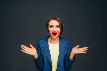 Amazing facial expression. Shocked young woman, dressing in business clothes making a surprised face and looking at camera while standing against grey background