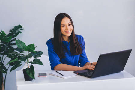 Portrait of attractive and confident businesswoman sitting at her workplace in office Zdjęcie Seryjne
