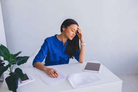 attractive young woman feeling tired, leaning her head on hand and closed eyes. Failure and Fatigue of office work