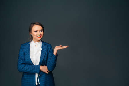 Look over there. Successful young woman, pointing copy space and smiling while standing against grey background