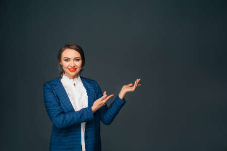 Look over there. successful young woman, pointing copy space and looking at camera while standing against grey background
