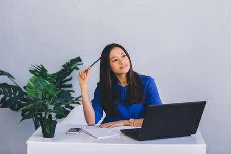 attractive and confident business woman waiting for inspiration, looking away while sitting at her workplace in office