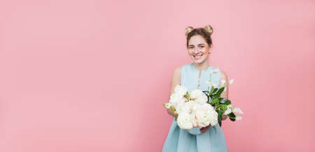 young trendy woman wearing turquoise dress holding bunch of flowers while standing on pastel pink color background. Femininity and beauty