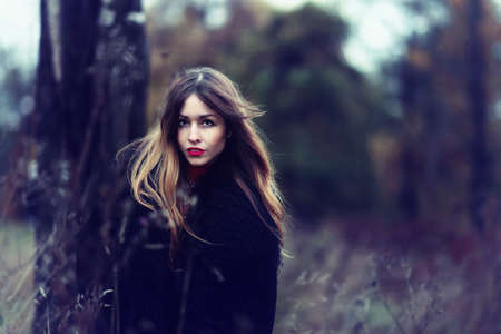 young fashionable woman in colourful autumn forest photo