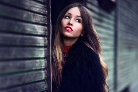 young fashionable woman staying near the wooden wall photo