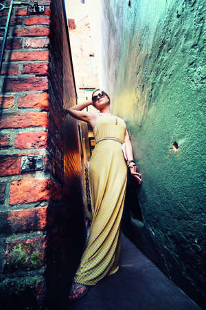 yellow dress young woman stating between two walls photo