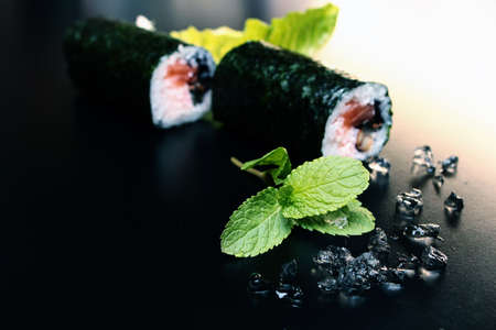 Sushi rolls on a black background with peppermint  photo