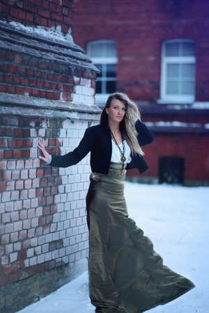 long skirt: Long hair blonde long skirt on the wind near red brick wall
