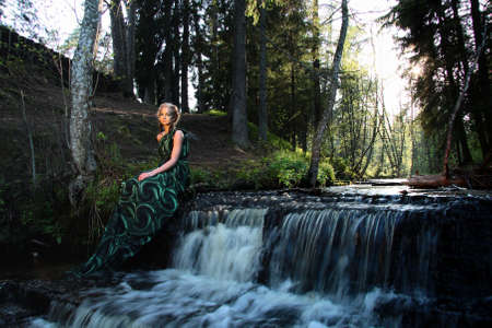 babyface: alone young nymph woman near waterfall in the forest Stock Photo