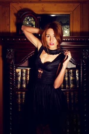 young brunette female black sexy dress in vintage interior photo