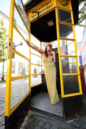 cell phone booth: young smiling female talking in yellow telephone booth yellow dress