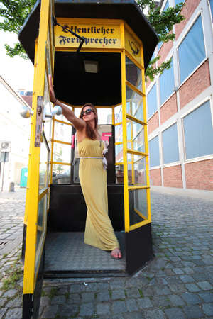 cell phone booth: yellow dress woman going out from yellow telephone box Stock Photo