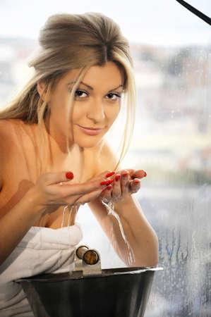 beautiful natural woman washing her face near window in spa photo