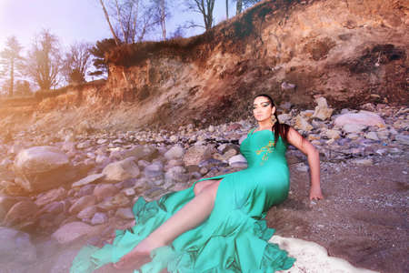 long turquoise dress beach sitting long hair woman  photo