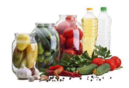 chiles picantes: Frascos de vidrio con pimientos, pepinos, tomates, junto a ellos - el ajo, el ají, perejil, eneldo, pepinos, tomates, aceite y vinagre