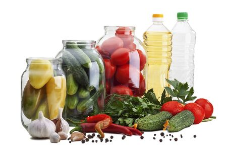 Glass jars with peppers, cucumbers, tomatoes, next to them - garlic, hot pepper, parsley, dill, cucumbers, tomatoes, oil and vinegar