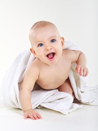 Sonriendo boysmiling poco chico tumbado sobre un fondo blanco Foto de archivo - 10747708