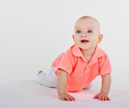 Smiling little boysmiling little boy lying on a white background photo