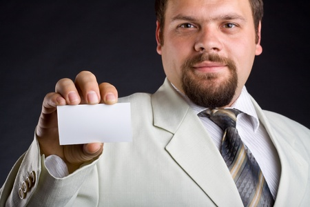 A man shows a business card. Focus on hand. Dark background.