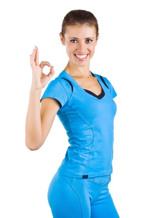 signaling: Girl in a blue sports suit shows ok, isolated on white background