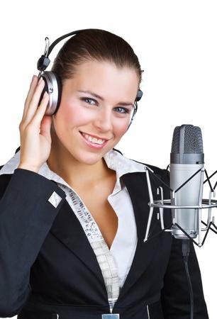 estudio de grabacion: Mujer sonriente delante de un micr�fono con auriculares, aislados en fondo blanco