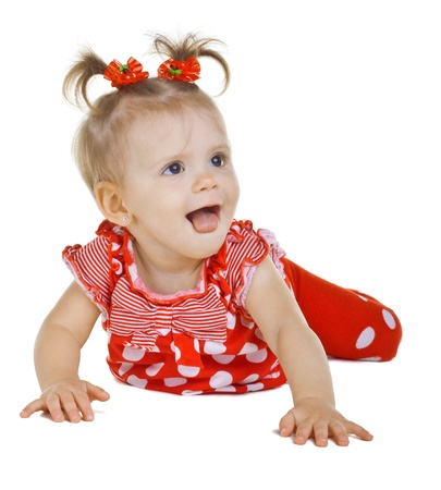 lies down: A small child in a red dress shows tongue, isolated on white background